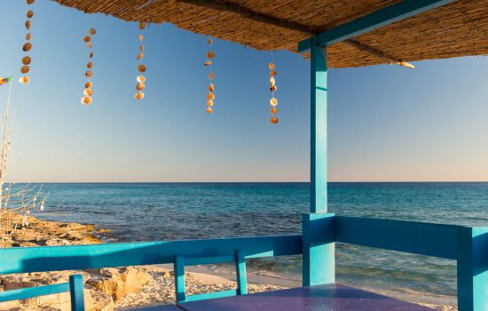 Colorful terrace with some chairs and table at Mediterranean sea in Formentera Island in summer. Some shell decorative objects are hanging from the roof. Balearic Islands, Spain.